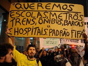 Figure 1: A sign reads 'We want schools, subways, trains, buses, ferries and hospitals to 'Fifa's standards'' (Agência Brasil)